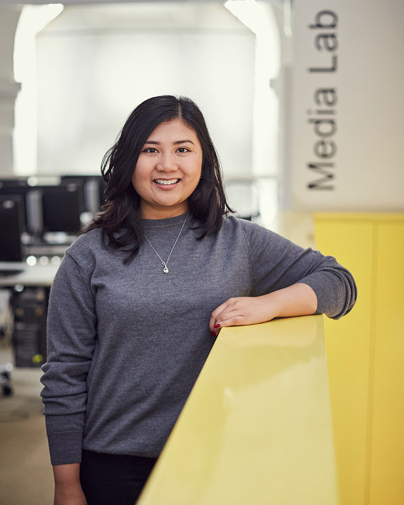 photo of alum Leana Felipe standing and leaning against a yellow railing and smiling at camera with long black hair and a long sleeved grey top in a room with many computer benches in the background
