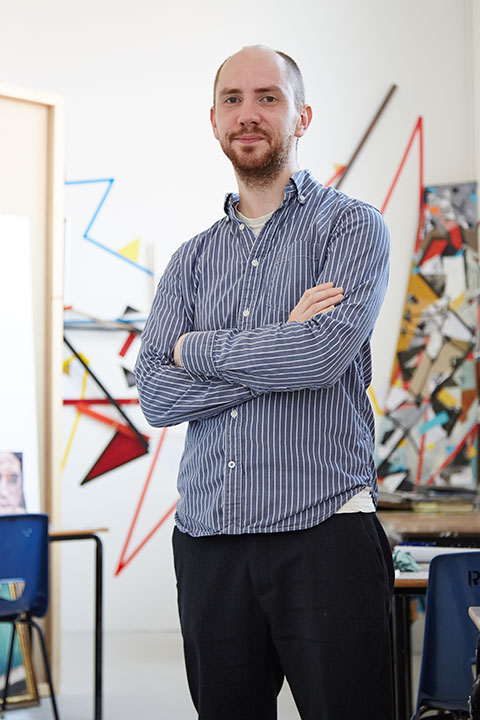 portrait photo of senior lecturer craig barber standing with arms crossed and looking at camera with short brown hair and a long sleeved vertically striped blue and white shirt
