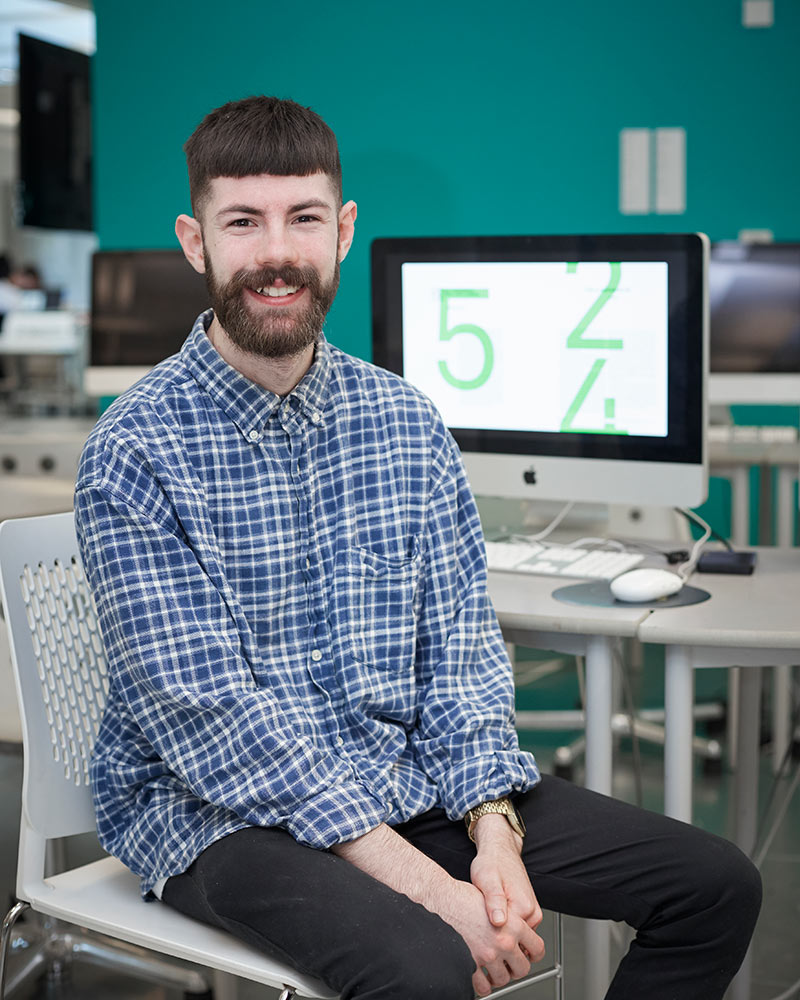photo of alum Matthew Longley sitting on a white chair and smiling at camera with hands crossed in lap and short brown hair wearing a loose blue and white checked buttoned shirt with several computers on benches in background
