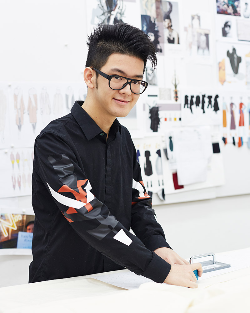 photo of alum Jerry Huang standing at design desk and smiling at camera with hands on fabric material and spiked black hair and thick black glasses and black long sleeved buttoned shirt in a room with a large board on the wall covered with design work