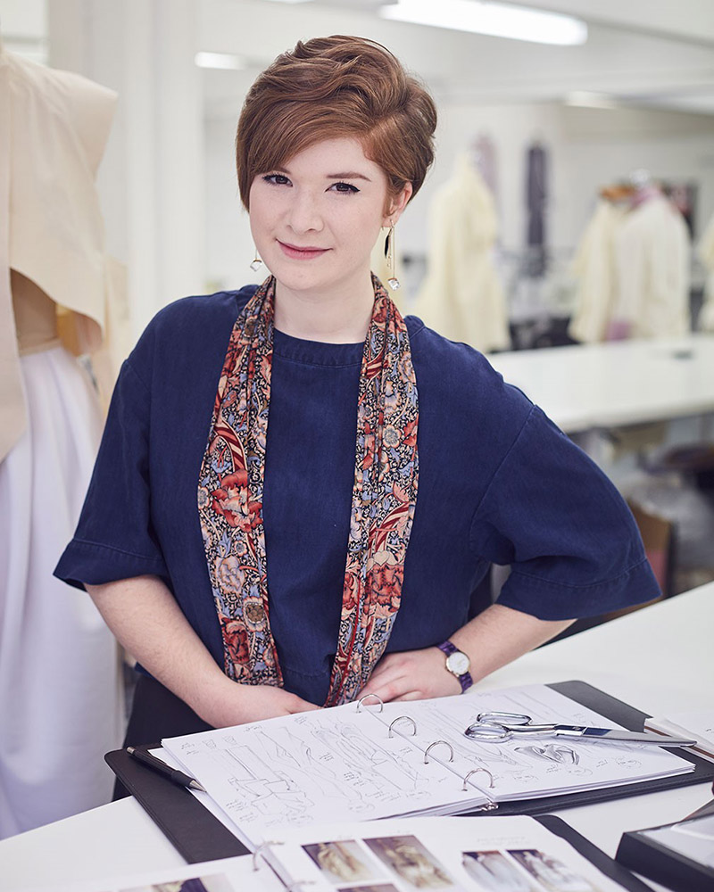 portrait photo of alum Mary Sinclair sitting at desk and smiling at camera with hands resting on desk and open sketchbook with short swept hair and a long floral scarf and a long denim top