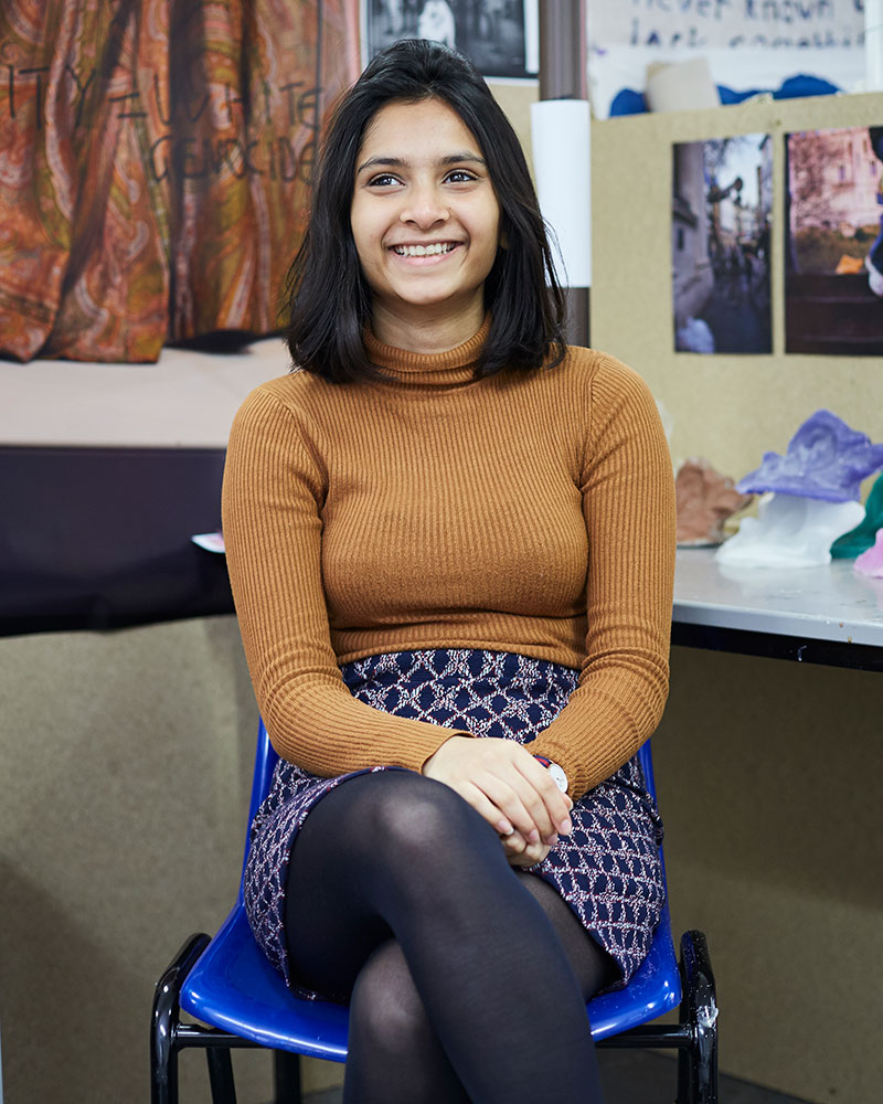 portrait photo of alum Alveera Rahman sitting in chair and smiling away from camera with black medium hair and brown long sleeved jumper