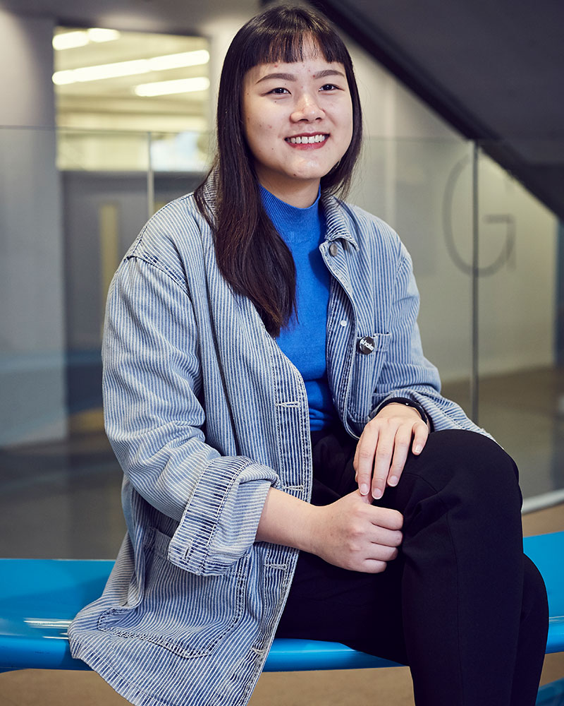 photo of alum Tsu-Ann Wong sitting on a blue bench and smiling while looking away from camera with long black hair and long blue and white vertically striped shirt with a short glass wall in the background