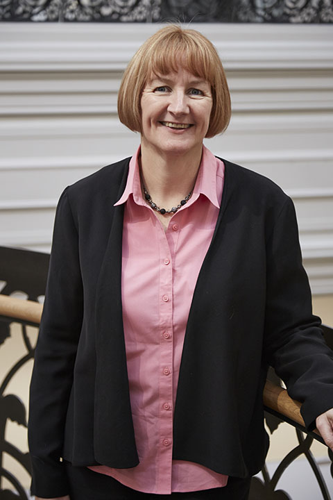 photo of Professor Hilary Carlisle smiling at camera with arm resting on railing with red medium hair and a black open shirt jacket