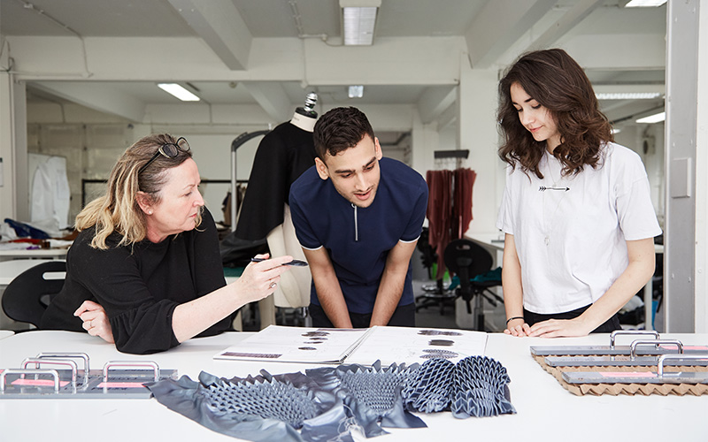 photo shows three people standing and looking at a sketchbook laid on a white table with several folded fabric samples and tools for pressing patterns into fabric spread out in a large studio room