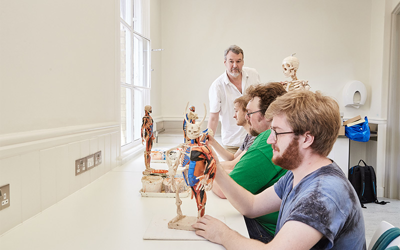 photo of 3D modelling studio shows a tall white room with a white desk against a wall and three students sitting in chairs and working on wax anatomical models of humanoid figures with a lecturer standing next to them and inspecting the work
