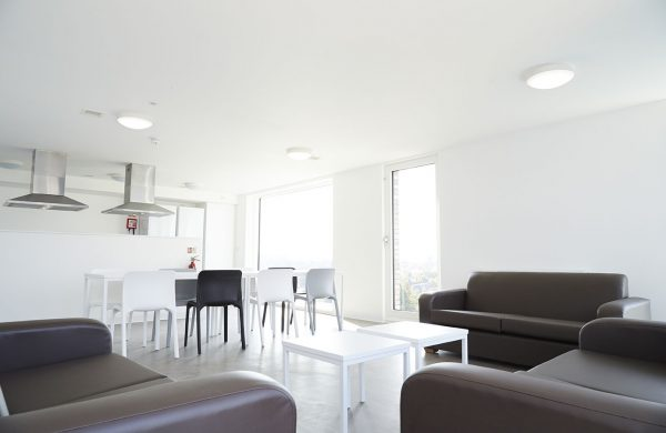 Communal kitchen - photo of wide white room with tall and wide floor length windows with brown leather sofas in foreground, a white table and chairs in the midground and extractor fans for the kitchen in the background