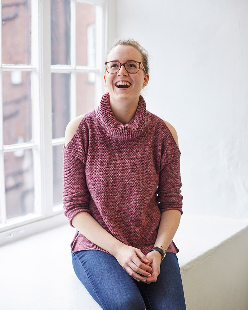 photo of alum leoni lessmann sitting on a ledge next to a window and smiling whilst looking up and with tied back hair and glasses with a rolled neck knitted jumper and crossed hands