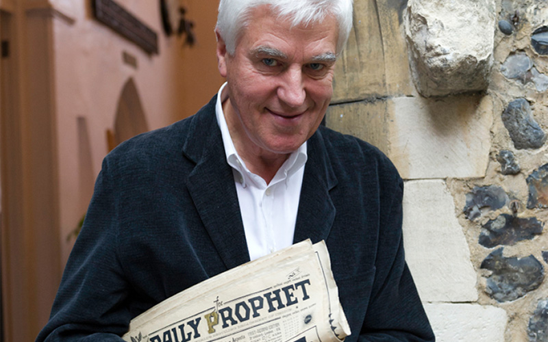 Photo of honorary doctorate stuart craig holding prop daily prophet newspaper and leaning next to stone wall arch