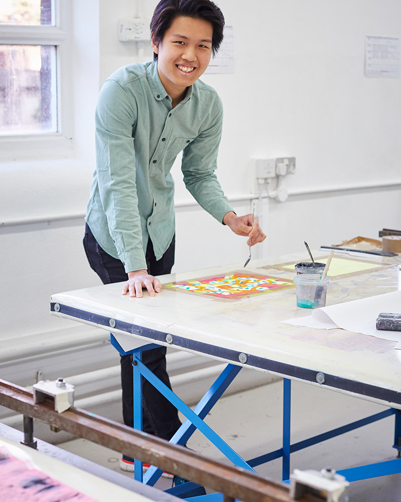 photo of alum Brandon Tan leaning over a desk and holding a spoon and smiling at camera with swept black hair and a denim buttoned shirt in a design studio with white walls and a window