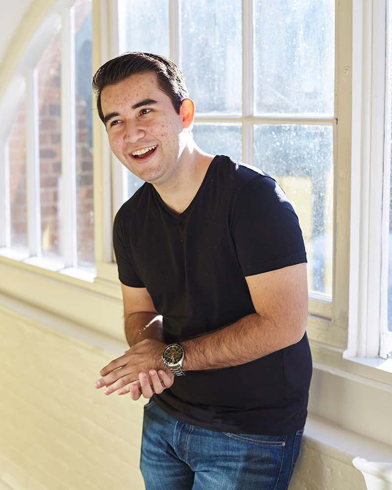 photo of alum Jose Fernandez looking up and smiling with combed black hair and wearing a black t-shirt with a wide bright window in the background
