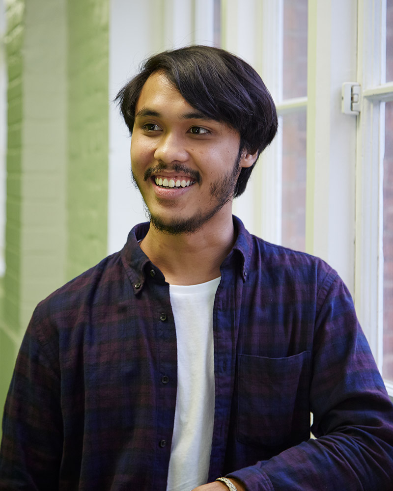 photo of alum Fahim Fadzlishah smiling and looking away from camera with arm leant against wall and short swept black hair and an open checkered red and blue shirt with window in background