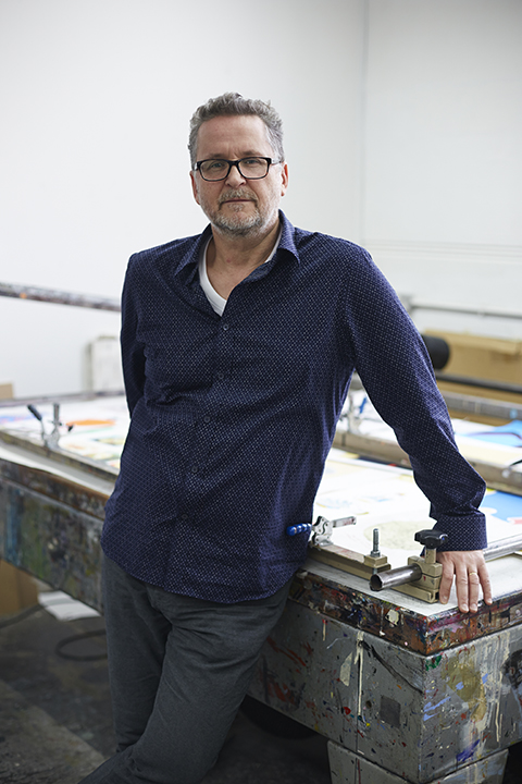 photo of course leader Carl Rowe standing with arms leant against a printing table and looking at camera with short hair and a blue shirt with a small lattice print