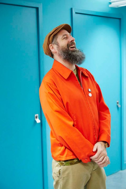 portrait photo of senior lecturer Nigel Aono-Billson laughing and looking away from camera with a brown flat cap and an orange zipped long sleeve jacket