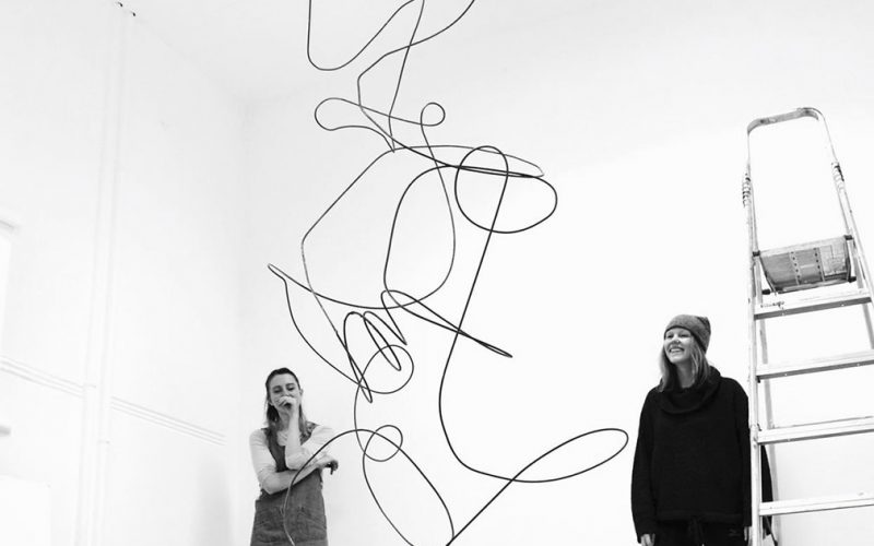 black and white photo of a large white room with a hanging wire piece warped into various shapes and curves with two people standing in the background and smiling