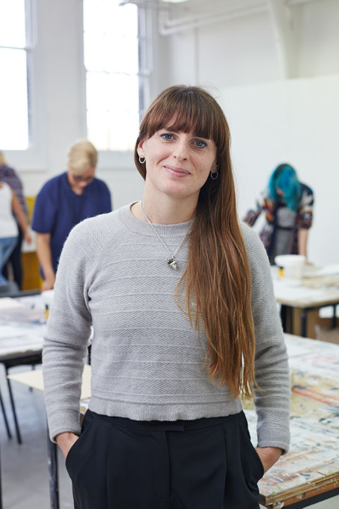 portrait photo of lecturer Sarah Longworth-West standing with hands in pockets and smiling at camera with long brown hair and a long sleeved patterned knit jumper