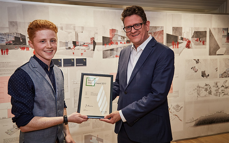 photo shows a student with short hair in a waistcoat and shirt with a man with short hair, thick rim glasses and a suit both holding a framed award certificate with a long wall of work in the background