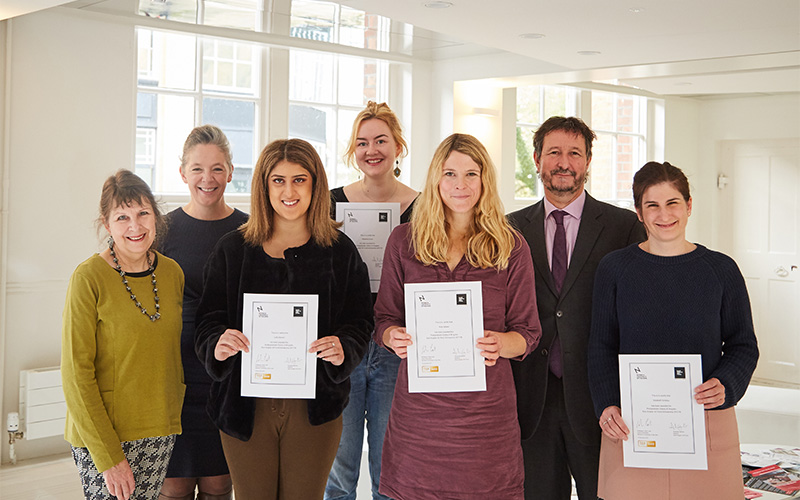 photo shows several students holding award certificates and smiling at camera with two older women on the left and professor john last to the right in the back row in a tall white room with bright light shining through windows