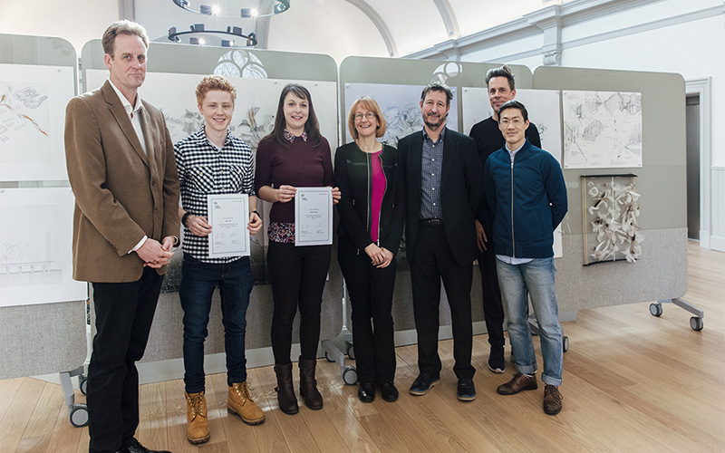 photo shows two students with award certificates smiling at camera with a tall man with swept hair looking at camera and professor hilary carlisle and professor john last and another man standing side by side with a tall man standing behind with boards of design work in background
