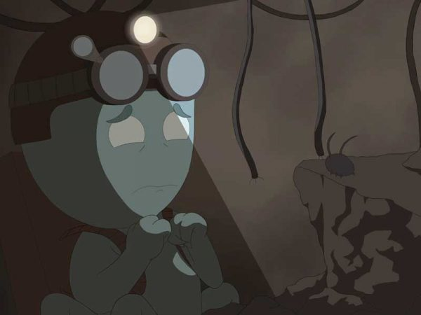 - Image of a green character in a dark room designed by NUA Animation student Sian Hayes