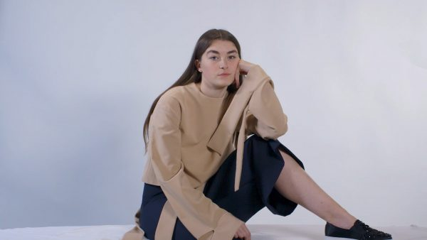 Sophie Chittock - Image of a female model sitting on the floor, looking to camera wearing tailored garments
