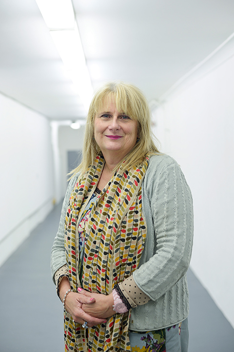 portrait photo of course leader Jill Rodgers standing with hands crossed and smiling at camera with long blonde hair and a leaf patterned scarf and a light green cardigan