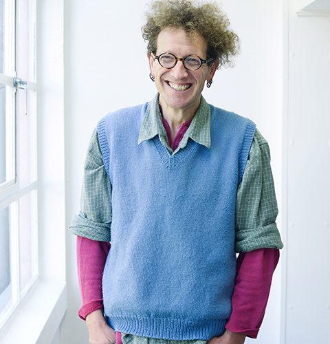 portrait photo of lecturer Nigel Bousfield standing with hands in pockets and smiling at camera with curly blonde hair and round brown glasses with a blue sweatervest and plaid green and white rolled sleeve shirt and a long sleeve pink undershirt
