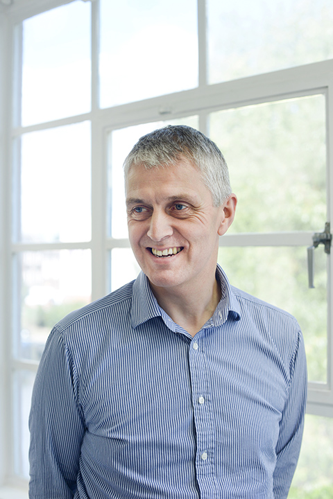 portrait photo of lecturer Nigel Coton standing and smiling away from camera with short white hair and a vertically striped white and blue long sleeved shirt