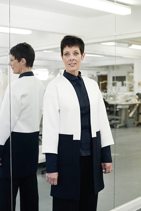 portrait photo of associate professor and course leader Sue Chowles standing next to tall wall of mirrors and smiling whilst looking away from camera with short black hair and a white and blue coat jacket