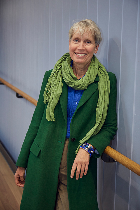 portrait photo of lecturer sharon tolaini-sage leaning against railing and smiling at camera with short blonde hair and a green scarf and a long green coat