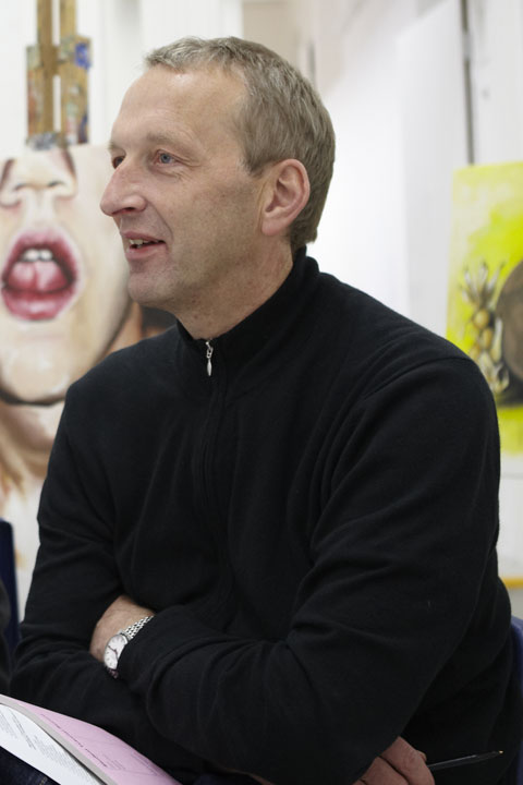 portrait photo of senior lecturer simon granger sitting with arms crossed and looking away from camera with short blonde hair and a long sleeved black jumper