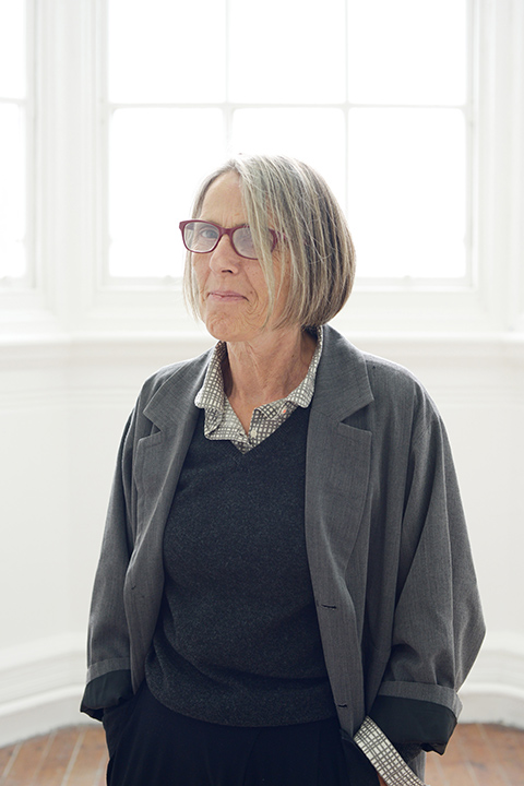 portrait photo of Research Supervisor Victoria Mitchell standing with hands in pockets and smiling at camera with medium blonde hair and red glasses and a grey loose open shirt jacket