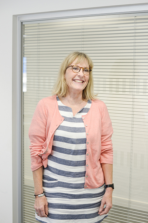 portrait photo of associate lecturer vicki winteringham standing with arms by side and smiling away from camera with medium blonde hair and light brown glasses and a blue and white horizontally striped dress and rolled pink cardigan