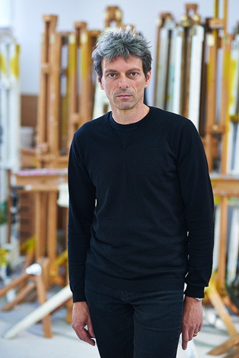 photo of senior lecturer Professor Krzysztof Fijalkowski standing with arms by side and looking at camera with grey short hair and a long sleeved black top
