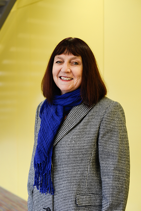 portrait photo of senior lecturer Professor Suzie Hanna standing with arms by side and smiling at camera with medium dark brown hair and a blue scarf and a buttoned black and white patterned coat