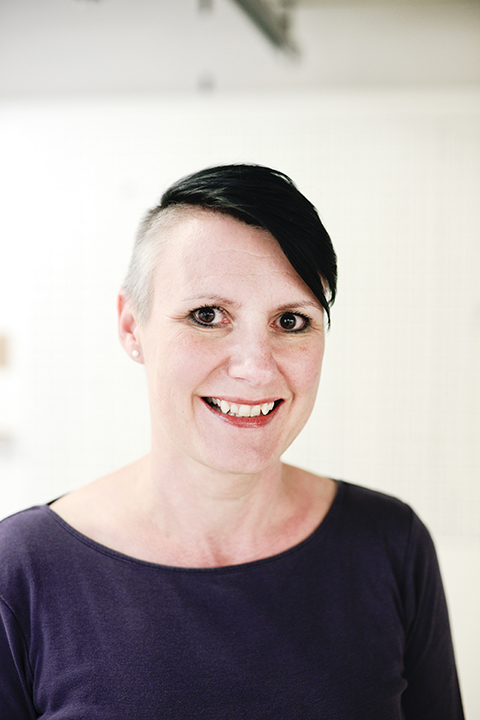 portrait photo of senior lecturer Sarah Horton smiling at camera with cropped black hair and a dark blue top