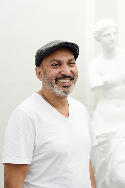 portrait photo of lecturer Suri krishnama smiling and looking away from camera with grey flat cap and a white t-shirt