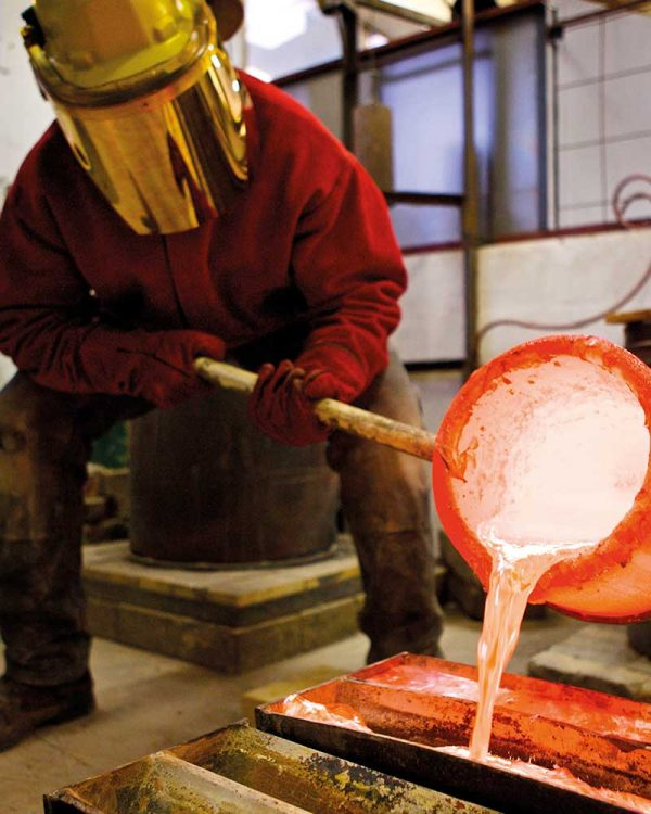- Image of a man wearing a gold protective mask is pouring molten metal into a cast