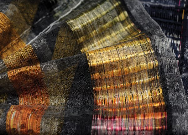Bethany Franks - Image of embrodiered material featuring the colours grey, yellow, orange and red