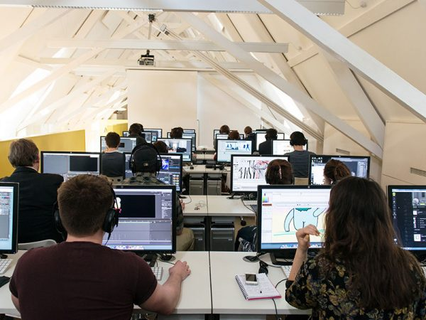 - Image of students working on computers in a media lab