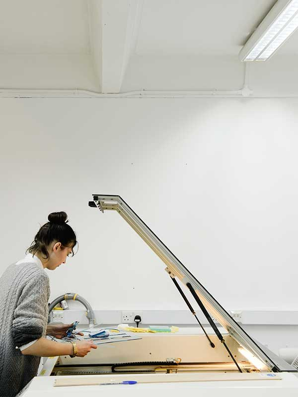 - Image of a female NUA student leaning under the hood of a laser cutting machine