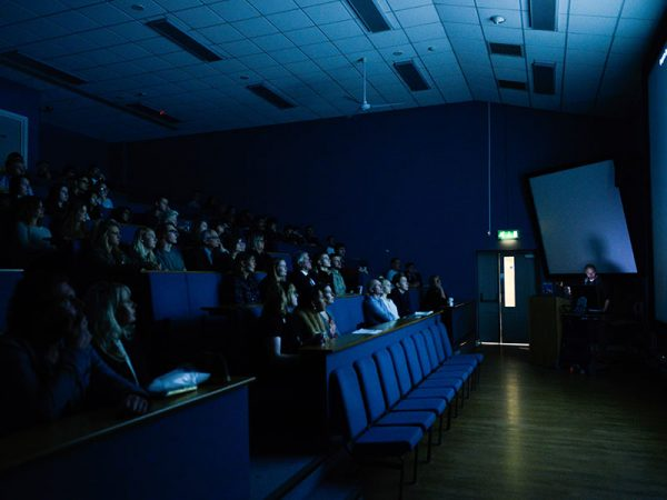 - Image of the NUA lecture theatre with people seated and someone presenting in front of the audience