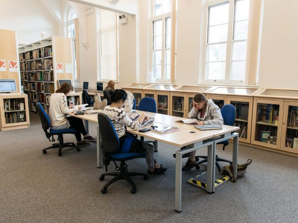 - Image of students working in a library reading books on a large desk