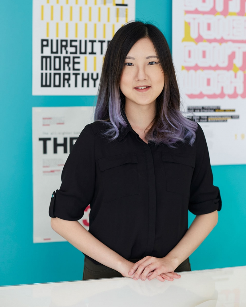 photo of alum Marissa Lim standing with hands resting on a table and smiling at camera with dark brown hair with lilac tips weawring a black rolled sleeve shirt with blue wall with graphic design work in background