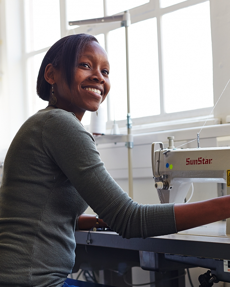 Naomi Wambugu MA Fashion student at sewing machine in Fashion Workshop