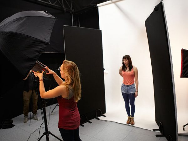 - Image of two students taking a photograoh in a photography studio