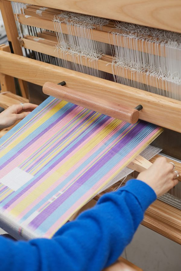 - Rebecca Hiscock, BA Textile Design student at Norwich University of the Arts on a loom in the textiles workshop