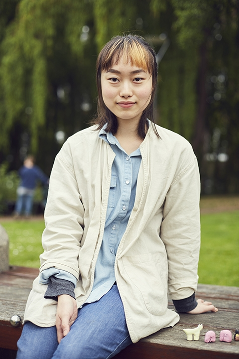 Sinae Park at Norwich University of the Arts outside on a bench