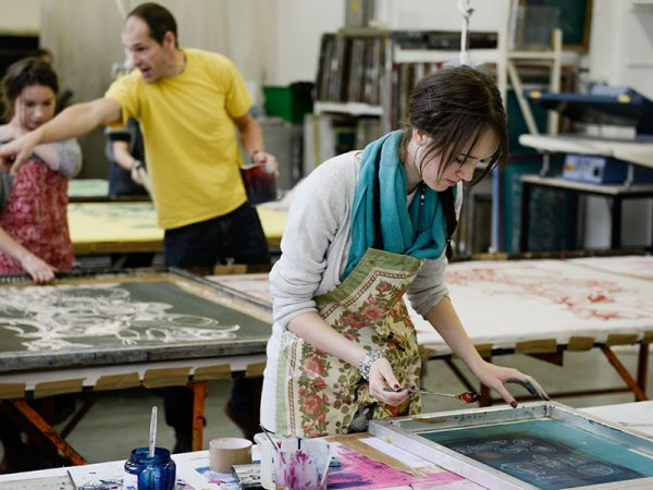 - Image of a student works on a screen in a printing studio