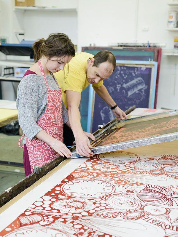 - Image of a student and a turor looking at a textiles screen